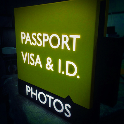 A photo ID sign featuring brightly lit letters on a green background